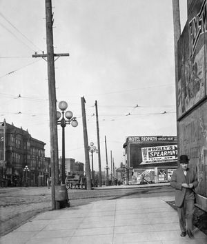 """THEN: In 1910, an estimated date for this look north on First Avenue across Virginia Street, the two corners on the east side of the intersection were still undeveloped — except for signs. The Terminal Sales Building, seen far right in Jean Sherrard's repeat, did not replace the billboards that crowd the sidewalk near the man walking in the """"then"""" photo until 1923. Now, the Denny Regrade has buildings that reach much higher than the lost Denny Hill."""
