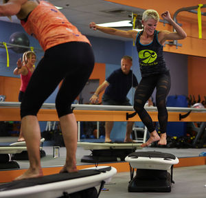 Instructor Laurie George, right, busts a move during an indoor surfing class as students try to keep up.