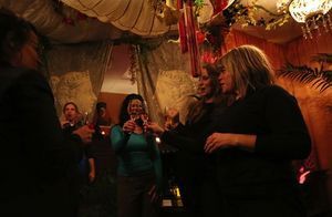 "Christi Meshell, center, leads a toast at a fragrance party she hosted at her Bellevue studio. Perfume-makers Nikki Sherritt-Lewis, far right, and Karyn Gold-Reineke, second from right, attended. Twelve fragrance-makers each had to produce an aroma based on a well-known local song. Meshell called the evening ""The Experience Perfume Project."""