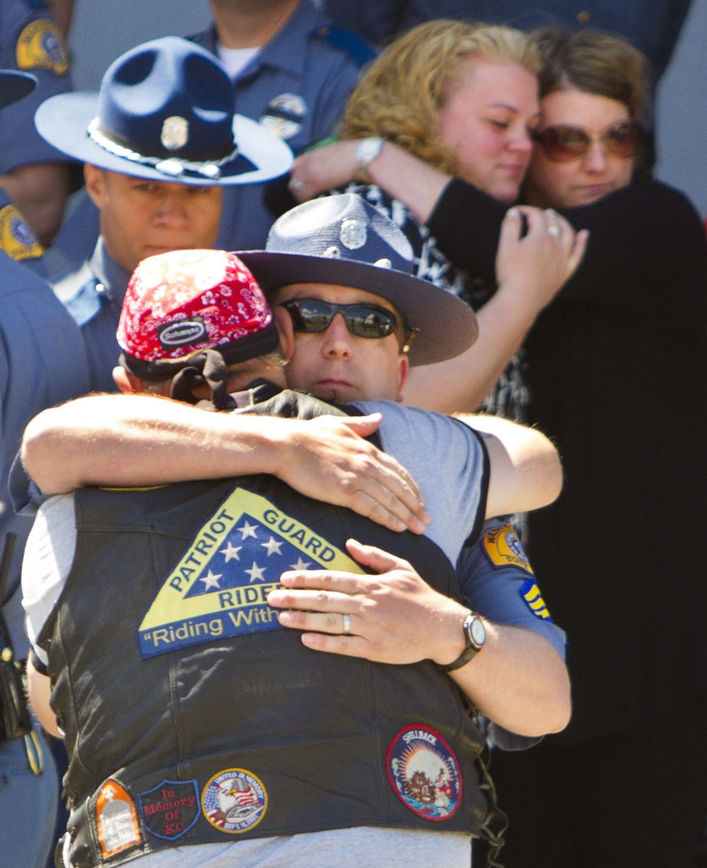 Bryan Lipscy, a member of the Patriot Guard Riders, hugs Washington State Trooper Chris Caiola after the body of Trooper Sean M. O'Connell, who was killed while on duty when his motorcycle was struck by another vehicle Friday evening, was brought to the Solie Funeral Home by a police escort on Sunday afternoon in Everett, June 2, 2013. Several members of the Patriot Guard Riders were on hand to salute the hearse carrying O'Connell's body as it drove past.  (Mike Siegel / The Seattle Times)