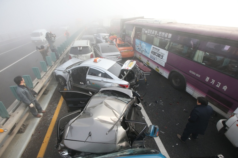 Damaged vehicles sit on Yeongjong Bridge in Incheon, South Korea, Wednesday, Feb. 11, 2015. Two people were killed and at least 42 were injured on Wednesday after a pileup involving about 100 vehicles in foggy weather on the bridge near the Incheon International Airport, South Korean officials said.(AP Photo/Yonhap, Suh Myung-gon) KOREA OUT