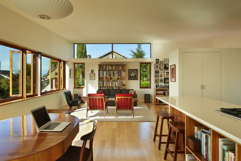 Julia Kuskin and Joel Bell desired an affordable home that took advantage of the views and light. Architect Chris Serra offered up plenty of both. The west wall of the main living space, on the second floor, is lined with picture windows. To save money, Kuskin took notes during weekly construction meetings, a job usually reserved for the contractor. (Benjamin Benschneider)