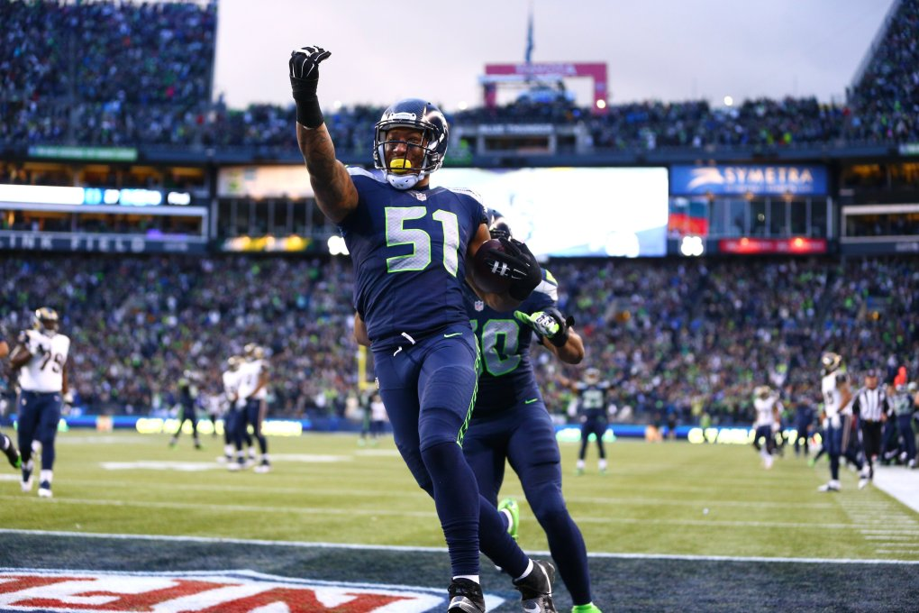 Bruce Irvin, shown scoring a touchdown against the Rams last season, continues to express his displeasure in his current contract situation and told one outlet Wednesday night he plans to play for the Falcons in 2016.  (John Lok / The Seattle Times)