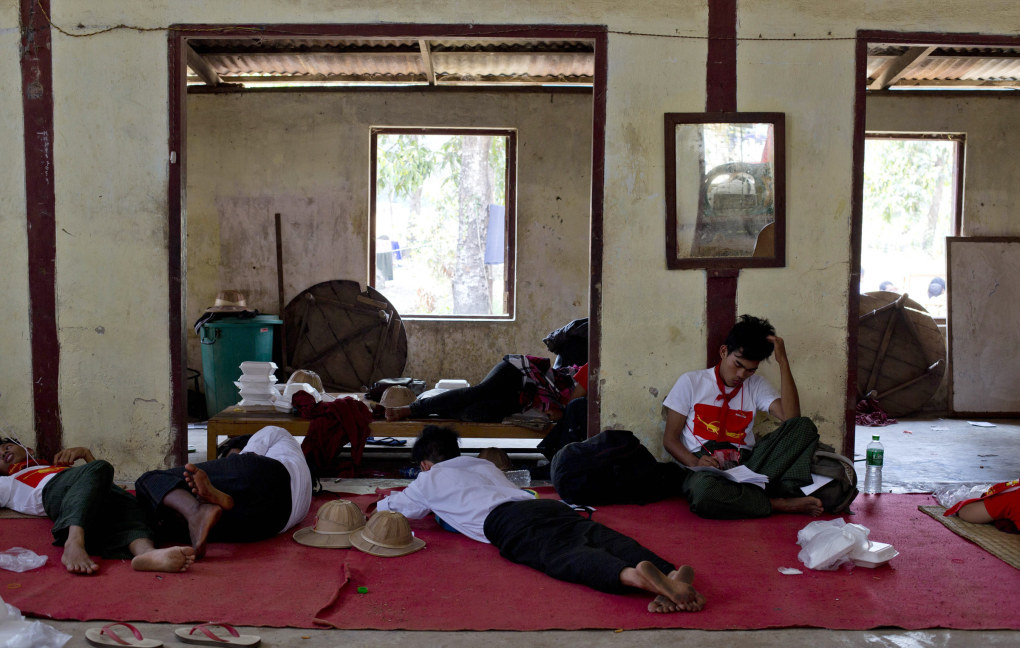 Student protesters lie on a monastery floor after police surrounded the monastery preventing them from proceeding with a protest march to Yangon from Letpadan, north of Yangon, Myanmar, Monday, March 2, 2015. Truckloads of police prevented hundreds of students from marching onward to Myanmar's old capital Monday to protest a new law that they say will curb academic freedom. (AP Photo/Gemunu Amarasinghe)