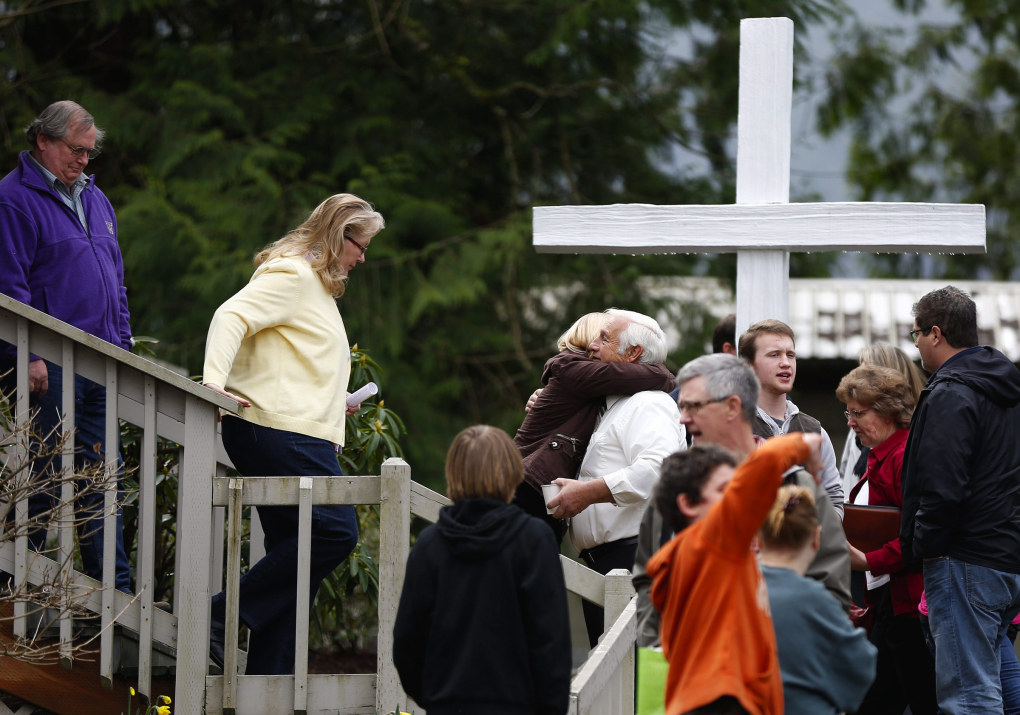 "People hug as they leave the Sunday community service at the Oso Community Chapel on Sunday, March 30, 2014. ""We may be knocked down but we're not knocked out,"" said Pastor Gary Ray in his sermon. Periods of rain and wind have hampered efforts the past two days, with some rain showers continuing in the afternoon. (Lindsey Wasson / The Seattle Times)"