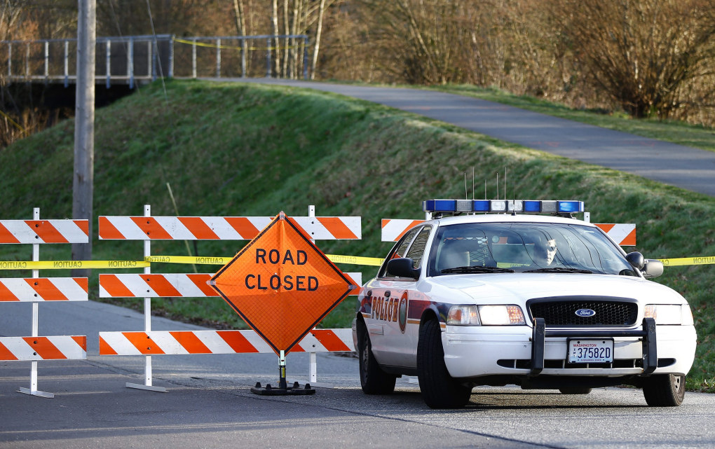 An Arlington Police officer monitors the scene outside the closed off Haller Park, which looks over where the north and south forks of the Stillaguamish River merge, in Arlington on Sunday, March 23, 2014. (Lindsey Wasson / The Seattle Times)