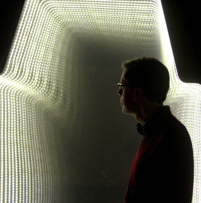 """EMP curator Brooks Peck pauses in front of an infinity window at the new exhibit """"Infinite Worlds of Science Fiction."""" (Greg Gilbert/The Seattle Times)"""