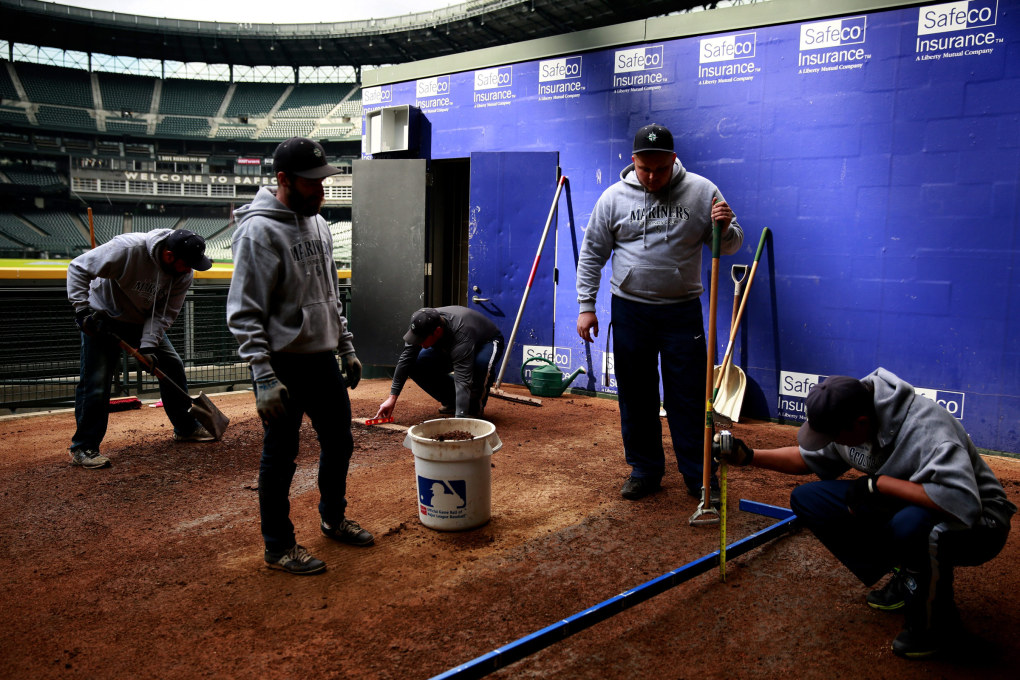 Groundskeepers work inside of the Mariners bullpen. (Erika Schultz / The Seattle Times)