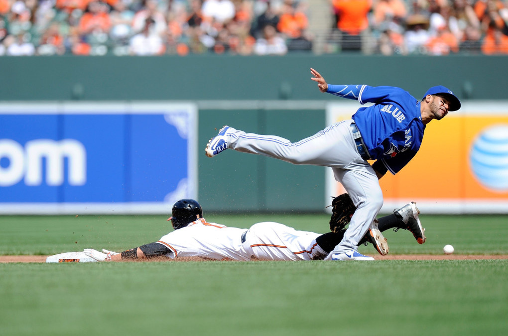 Manny Machado #13 of the Baltimore Orioles steals second base in the second inning as the throw gets away from Devon Travis #29 of the Toronto Blue Jays at Oriole Park at Camden Yards on April 12, 2015 in Baltimore, Maryland.  (Photo by Greg Fiume/Getty Images)