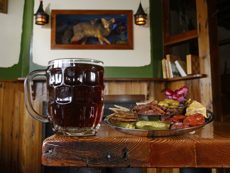 A pint and a platter of snacks at the Cozy Nut Tavern, a quirky dive bar in Greenwood.  (Mark Harrison/The Seattle Times)