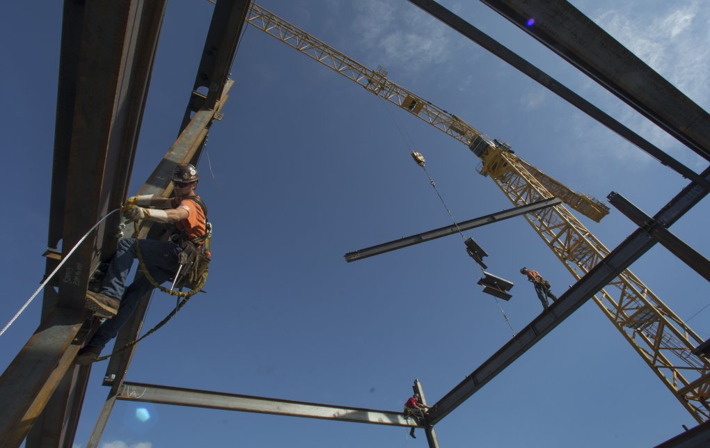An iron worker  helps erect steel on a 13-story  office building in South Lake Union. (Ellen M. Banner / The Seattle Times, 2014)