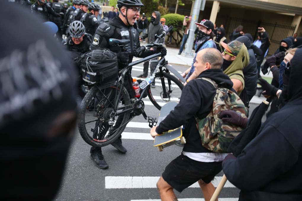 Tempers flare as police try to regain control of unruly May Day demonstrators, using mace and flash bang grenades to disperse the crowd, and tend to an officer.  (Dean Rutz / The Seattle Times)