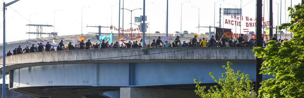 Several hundred demonstrators march toward Terminal 5 on the Harbor Island / Terminal 5 overpass on Monday morning.  (Mike Siegel/The Seattle Times)