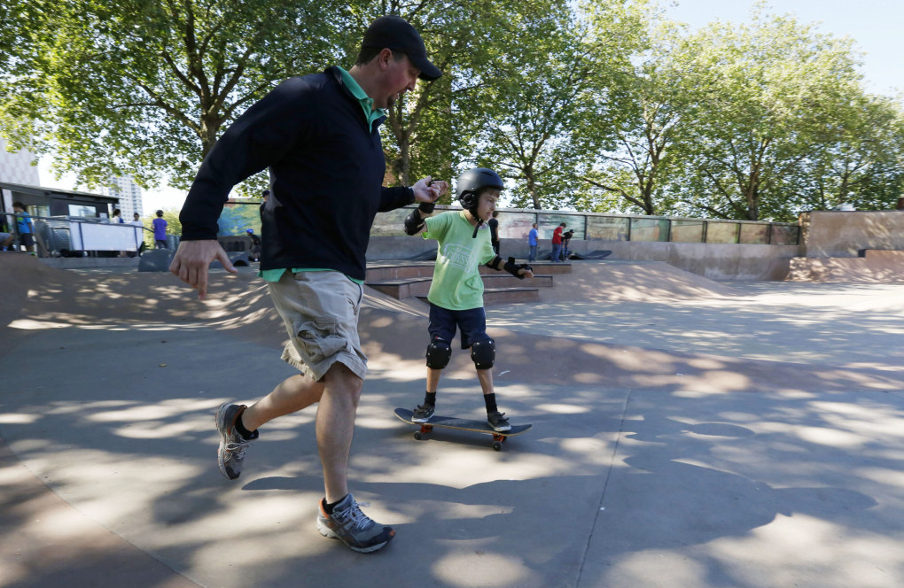 Josh Reynolds helps his son Gideon learn to skateboard at Seattle Center. (Alan Berner / The Seattle Times)