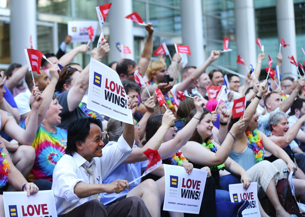 "Members of the Seattle Men's Chorus and Seattle Women's Chorus wave small flags and hold ""Love Wins"" signs during a marriage equality rally outside the Federal Courthouse in downtown Seattle.   (Lindsey Wasson / The Seattle Times)"