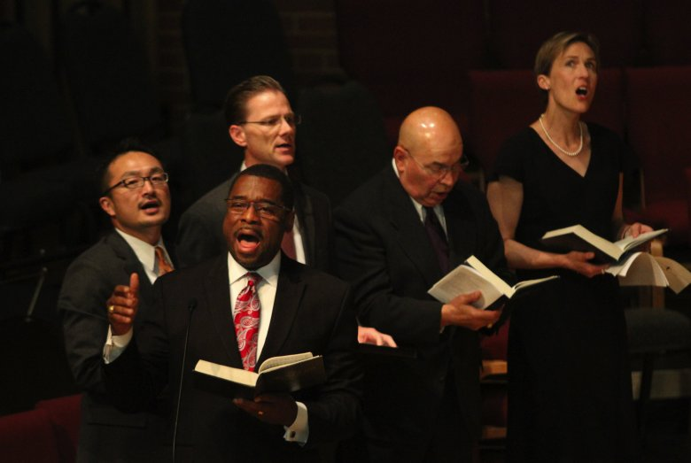 """Professor Stephen Newby led the singing of the hymn """"Great Is Thy Faithfulness."""" (Alan Berner/The Seattle Times)"""