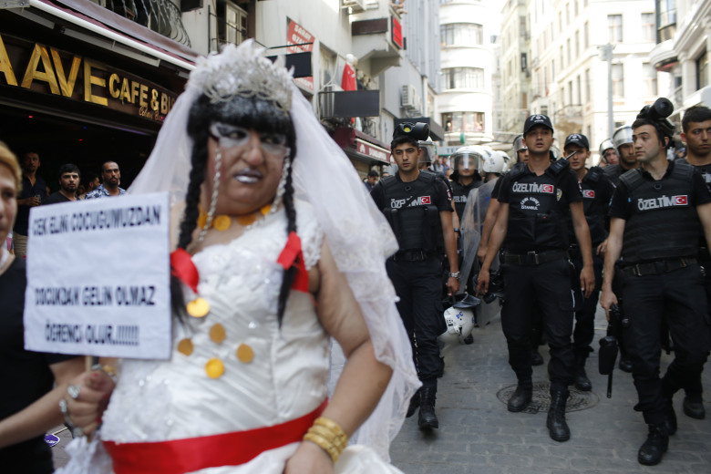 Turkish police walk as they push back participants of a Gay Pride event in support of  Lesbian, Gay, Bisexual and Transsexual (LGBT) rights in Istanbul, Sunday, June 28, 2015. Turkish police have used water cannons and tear gas to clear gay pride demonstrators from Istanbul's central square. It wasn't immediately clear why the police intervened to push the peaceful if noisy protest away from the area. Demonstrators regrouped a few blocks down the street and continued to dance and chant slogans against homophobia without any further clashes. (AP Photo/Emrah Gurel)