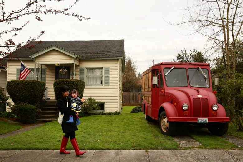 Leslie Dozono walks with daughter Lena, 2, near their home in Columbia City. Dozono had planned to return to work when Lena was 5 months old but couldn't find day care and changed her mind. (Erika Schultz/The Seattle Times)