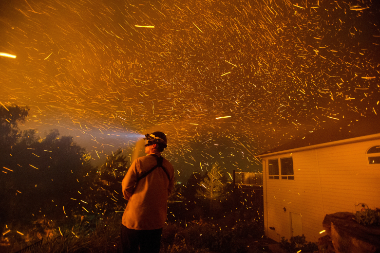 A Douglas County fire fighter sprays down the back of a home in Wenatchee, trying to protect it from burning embers flying off of a neighboring house on fire on Sunday night. (Don Seabrook / The Wenatchee World)