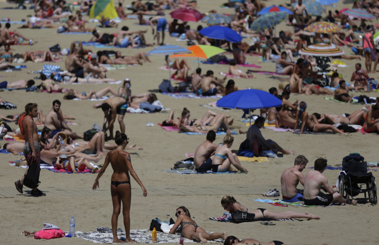 People sunbathe in a beach in Barcelona, Spain, Sunday, June 28, 2015. Weather stations across Spain are warning people to take extra precautions as a heat wave engulfs much of the country, increasing the risk of wildfires. The country's meteorological agency says a mass of hot air originating in Africa is moving northwards, bringing with it until at least Monday temperatures reaching 40 degrees centigrade (104 Fahrenheit). (AP Photo/Manu Fernandez)