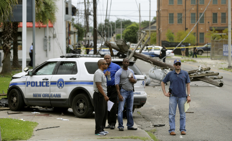 Investigators stand in front of a New Orleans Police department vehicle in which one officer was shot and killed while transporting a prisoner in New Orleans, Saturday, June 20, 2015. (AP Photo/Gerald Herbert)