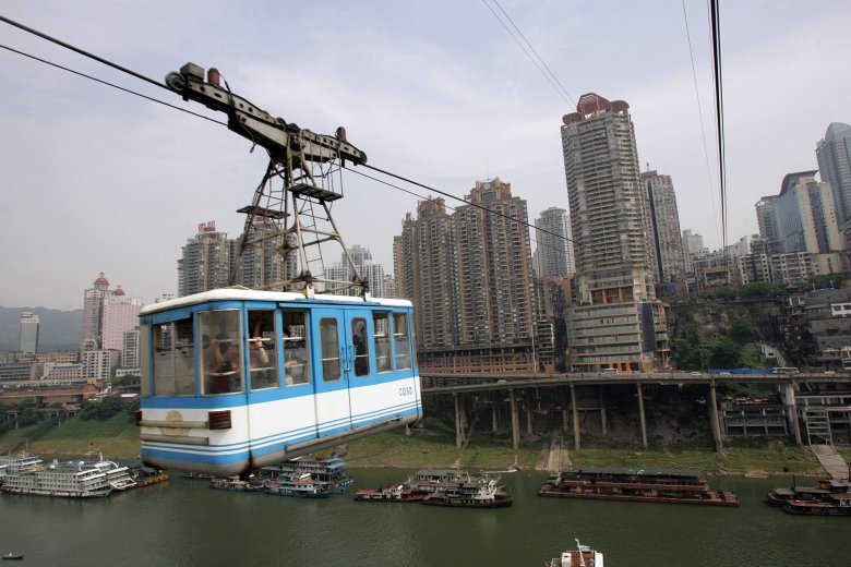 Tourists take a cable car ride across China's mighty Yangtze River, enjoying the view of the 3,000-year-old Chongqing city, built on top of steep hills squeezed onto a narrow strip of land between the Yangtze and the Jialing River, while located 1,000 kilometers (625 miles) inland, Chongqing may have one of the world's oddest locations for a big city, 16 May 2007.  The southwest Chinese municipality is taking advantage of a five-year-old government policy to lift economic growth in China's underdeveloped west, and has turned itself into one giant construction site, filling the air with dust and impenetrable noise, is home 32 million people.          AFP PHOTO (Photo credit should read STR/AFP/Getty Images) BEJ024