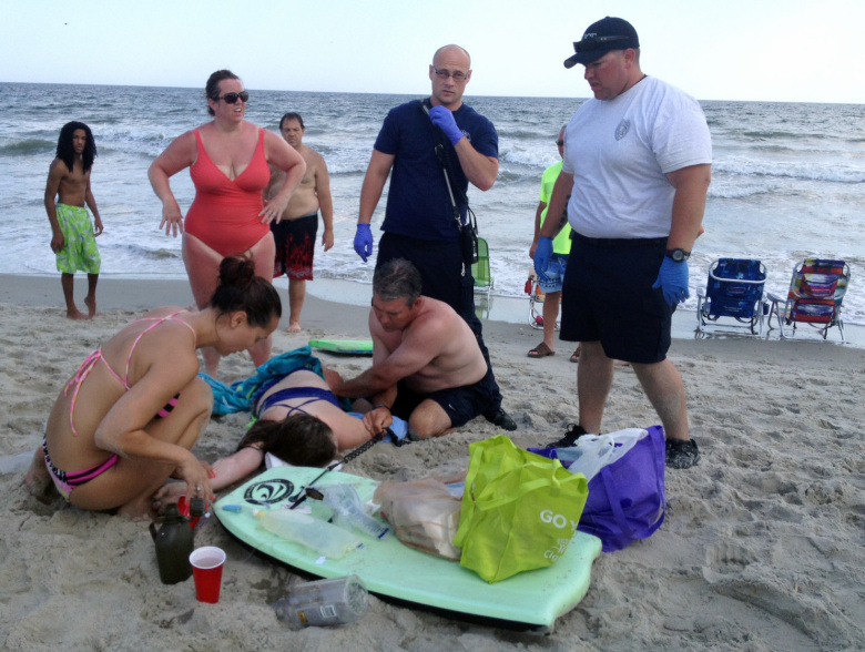People assist a teenage girl at the scene of a shark attack in Oak Island, N.C., Sunday, June 14, 2015. Mayor Betty Wallace of Oak Island, a seaside town bordered to the south by the Atlantic Ocean, said that hours after the teenage girl suffered severe injuries in a shark attack Sunday a teenage boy was also severely injured. (Steve Bouser/The Pilot, Southern Pines, N.C. via AP) MANDATORY CREDIT