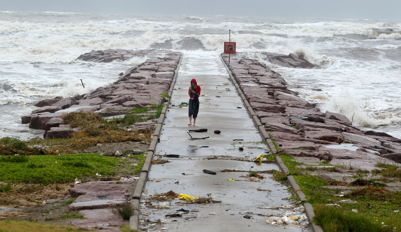 CORRECTS TRANS REF TO TXCOR AND ADDS MBO – A woman walks back from watching the waves roll over the end of the 29th Street Galveston rock groin Tuesday, June 16, 2015, in Galveston, Texas as Tropical Storm Bill makes landfall near Matagorda Bay on the Texas Gulf coast. (Rachel Denny Clow/Corpus Christi Caller-Times via AP)