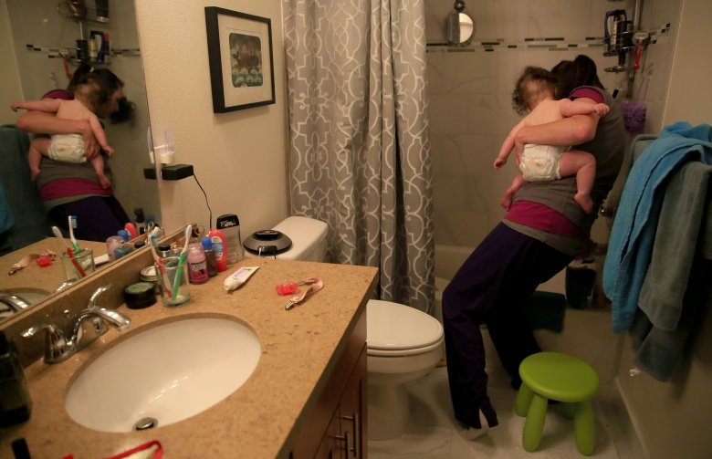 Still wearing her scrubs, Homeier runs a bath for Helen. She works two 12-hour shifts on the weekends to save money on child care. (Erika Schultz/The Seattle Times)
