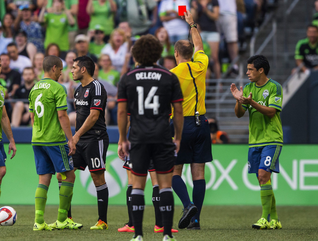 DC United forward Fabian Espindola is issued a red card by referee Silviu Petrescu for a foul in the first half Friday.  At right is Seattle's Gonzalo Pineda.  At left Seattle's Osvaldo Alonso.   (Dean Rutz / The Seattle Times)