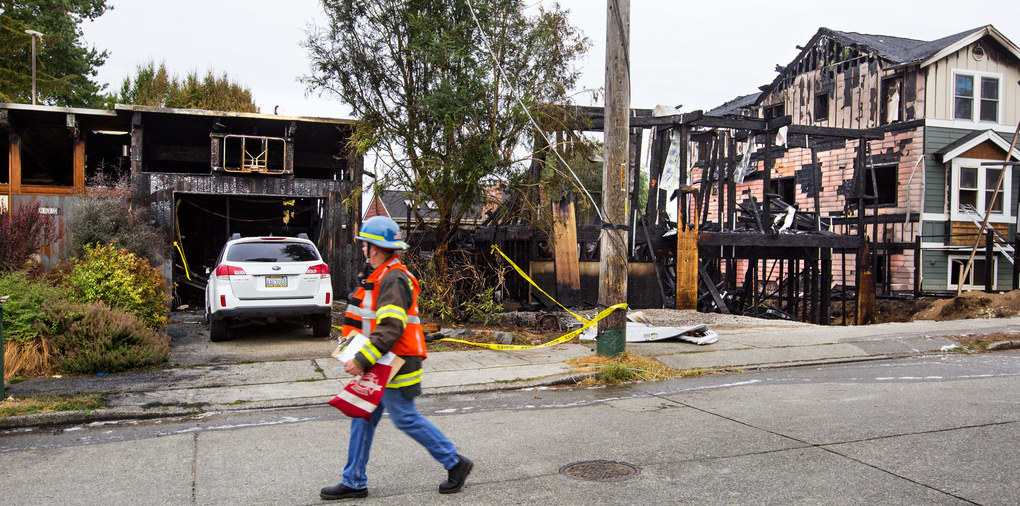 """Three homes in the 8500 block of 8th Avenue Northeast in Seattle were burned during an early morning fire. Two of the homes were a total loss according to Seattle Fire Department spokesman Kyle Moore.  Moore said no one was injured in the house fires. """"We did rescue a pet bearded dragon lizard,"""" Moore said. """"We're still searching for a cat."""" The fire started at about 3 a.m. in a home under construction.   (MIke Siegel / The Seattle Times)"""