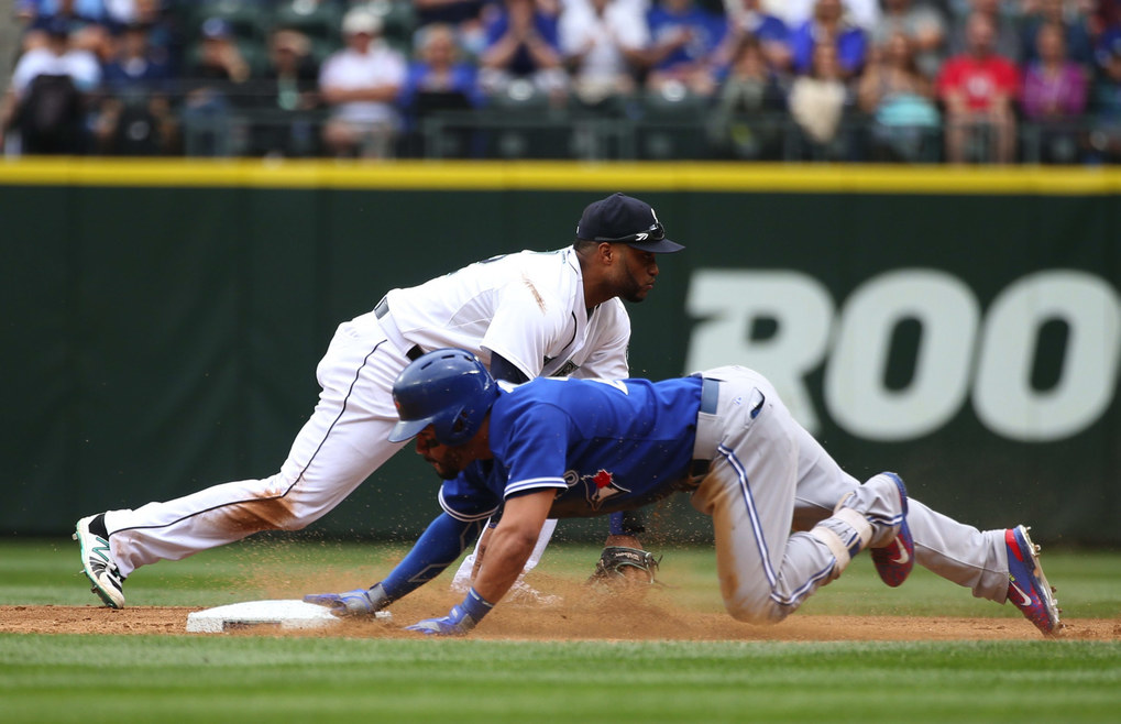 Mariners second baseman Robinson Cano scrambles past second as he tries to field an error from Seth Smith, allowing the Blue Jays' Devon Travis to get safely to third during the second of a three-game series against the Toronto Blue Jays at Safeco Field. (Lindsey Wasson / The Seattle Times)