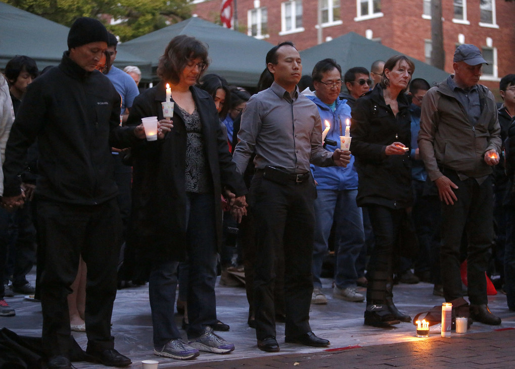 "Community members hold hands during a moment of silence at the memorial for Donald ""Donnie"" Chin.   (Sy Bean / The Seattle Times)"