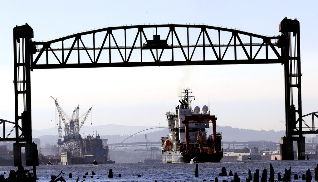 The  Shell  icebreaker Fennica heads back to Portland harbor, at left, after it was blocked on its way to Alaska by activists hanging from the St. Johns bridge in Portland, Ore., Thursday.  (Don Ryan / The Associated Press)