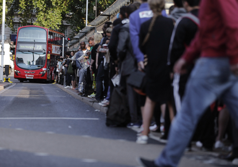 Commuters queue for buses as tube drivers are on strike in London, Thursday, July 9, 2015. Drivers and station staff were walking out for 24 hours from 6:30 p.m. (1730GMT) Wednesday in a dispute over pay and schedules when a 24-hour subway service starts on some lines later this year.The Underground handles 4 million journeys a day, and the strike by members of four unions will likely paralyze the capital's transport system, despite extra bus and river services. (AP Photo/Frank Augstein)