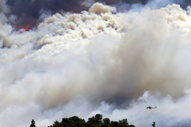 A helicopter operates over a fire in the eastern suburbs of Athens on Friday, July 17, 2015. The brush fire broke out on the outskirts of the Greek capital, burning across a hillside and blanketing parts of Athens in thick smoke. The blaze moved fast, fanned by strong winds and devouring parts of a verdant hillside popular with day-trippers. (AP Photo/Thanassis Stavrakis)