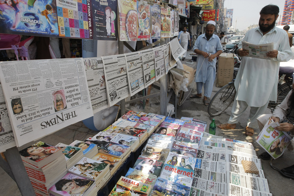 A man reads a newspaper at a news stand where local newspapers are displayed carrying headlines about the death of Taliban leader Mullah Mohammad Omar, in Peshawar, Pakistan, Thursday, July 30, 2015. Afghanistan's Taliban on Thursday confirmed the death of Mullah Omar, who led the group's self-styled Islamic emirate in the 1990s, sheltered al-Qaida through the 9/11 attacks and led a 14-year insurgency against U.S. and NATO troops. (AP Photo/Mohammad Sajjad)