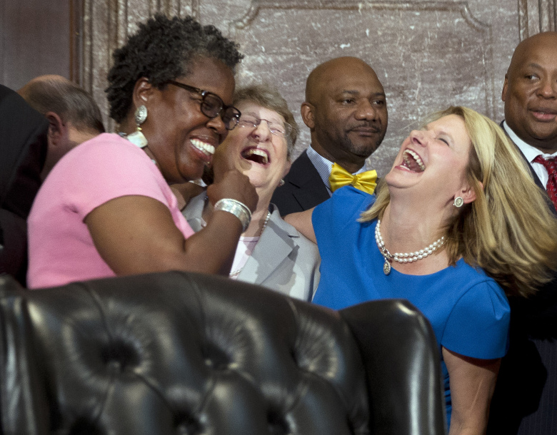 Rep. Gilda Cobb-Hunter, D-Orangeburg, left, laughs with South Carolina Supreme Court Chief Justice Jean Toal, center, and Rep. Jenny Horne, R-Summerville, before a ceremony where South Carolina Gov. Nikki Haley signed a bill into law, Thursday, July 9, 2015, at the Statehouse in Columbia, S.C. The law enables the removal of the Confederate flag from the Statehouse grounds more than 50 years after the rebel banner was raised to protest the civil rights movement. (AP Photo/John Bazemore)