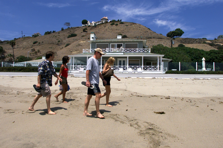 "FILE – In this July 27, 2002 file photo, beachgoers walk past Hollywood mogul David Geffen's home on Carbon Beach in Malibu, Calif. A public accessway to the beach was established next to Geffen's home in 2005. It may be called ""Billionaires' Beach,"" but the pristine views along one of Malibu's most exclusive coastlines are now more accessible. After a decade-long legal fight that pitted public access advocates against a wealthy homeowner who refused to build a path, the California Coastal Commission will open a third accessway a few hundred yards down the beach from Geffen's home Tuesday, July 7, 2015.(AP Photo/Damian Dovarganes, File)"