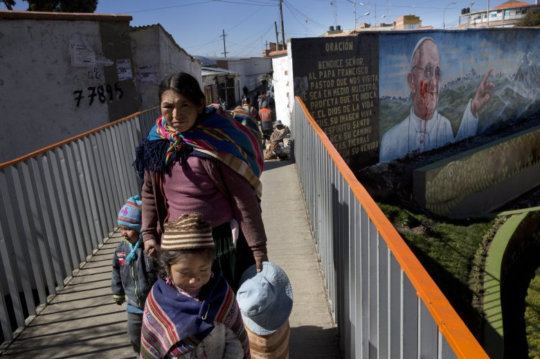 A woman walks her kids along a bridge where a mural, defaced, promotes the upcoming visit of Pope Francis in El Alto, Bolivia, Tuesday, July 7, 2015. The pope will arrive to Bolivia on Wednesday during his South American tour. (AP Photo/Rodrigo Abd)
