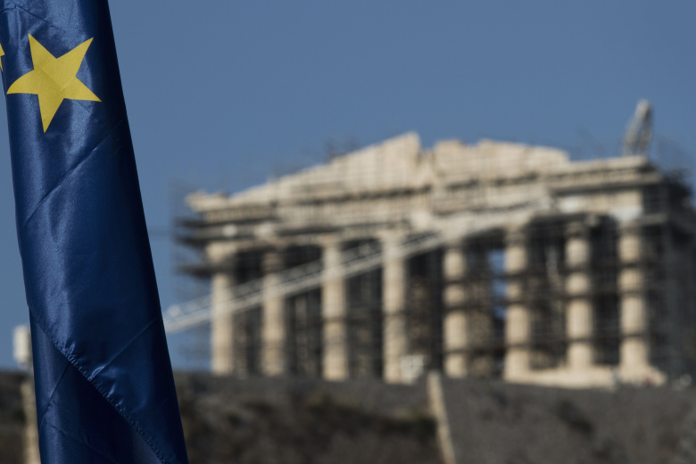 One of the stars of a European Union flag is seen in front of the ancient parthenon temple at the Acropolis hill in Athens, Monday, July 13, 2015. After grueling, often angry negotiations that tested the limits of European unity, Greece on Monday won a preliminary deal that averts financial catastrophe but also guarantees years more of hardship and sacrifice for its people. (AP Photo/Petros Giannakouris)