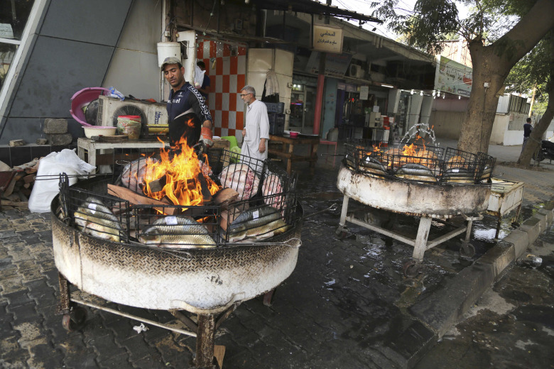 A street vendor cooks fish during in central Baghdad, Iraq, Thursday, July 16, 2015. The government declared Thursday an official holiday due to scorching temperatures. Health authorities have warned people not to expose themselves to the sun, with hospitals already receiving an overwhelming number of heat-related cases. (AP Photo/Karim Kadim)