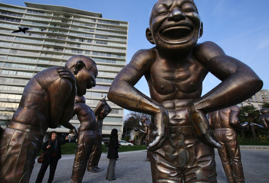 In this case, art is a laughing matter as a visitor to this installation by Yue Minjun checks out the figures in Vancouver, B.C. next to Stanley Park at English Bay. (Alan Berner / The Seattle Times)