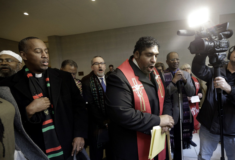 In this photo taken Wednesday, Jan. 28, 2015, Rev. William Barber II leads a group of demonstrators at the North Carolina General Assembly in Raleigh, N.C. His supporters describe Barber, 51, as a leader the likes of which the country hasn't seen since the Rev. Martin Luther King Jr. (AP Photo/Gerry Broome)
