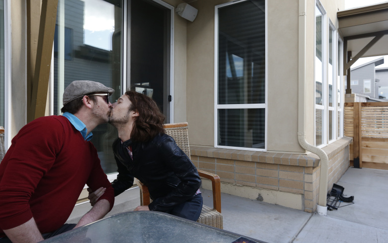 File – In this March 13, 2014 file photo, Dave Mullins, right, kisses his husband Charlie Craig, on the patio of their home in Westminster, Colo. The suburban Denver baker who refused to make a wedding cake for Mullins and Craig is to argue Tuesday, July 7, 2015 before the Colorado Court of Appeals that his religious beliefs should protect him from sanctions against his business. (AP Photo/Brennan Linsley, file)