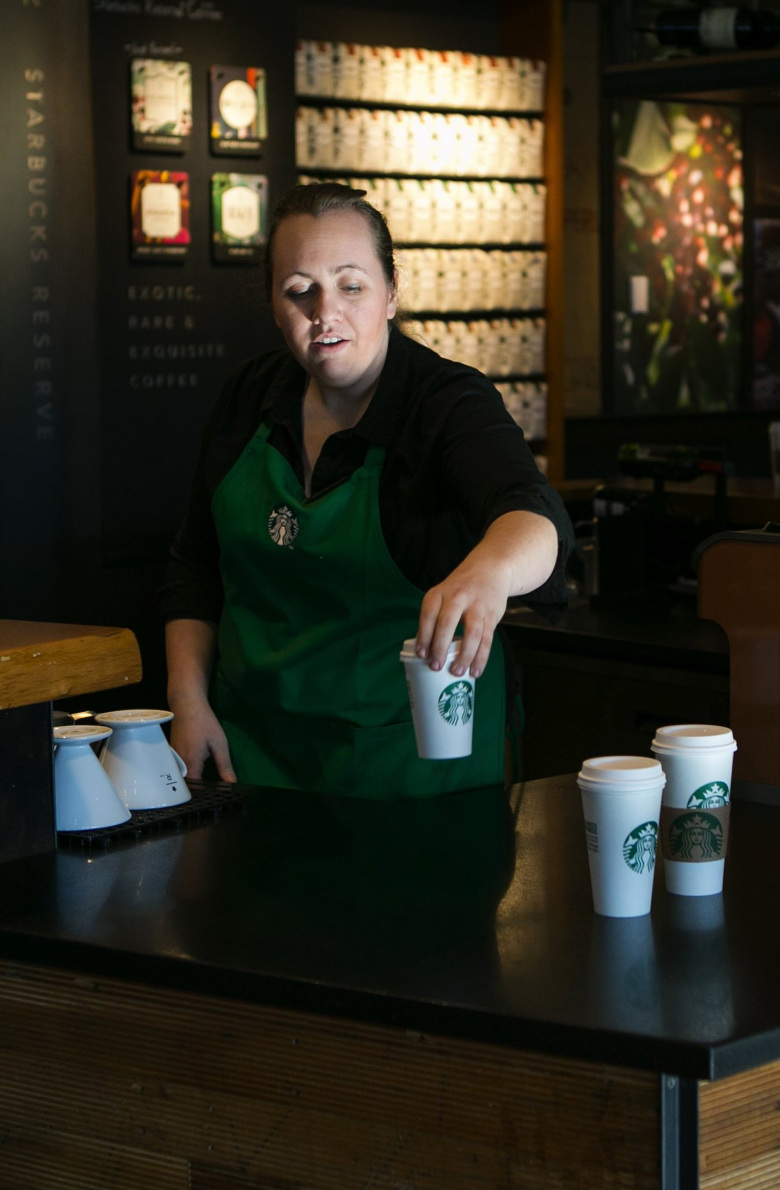 Starbucks shift supervisor Hailey Potter puts out drinks.  (Bettina Hansen / The Seattle Times)