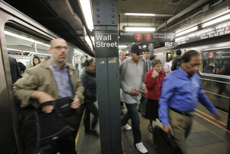 FILE – In this Wednesday, Oct. 8, 2014, file photo, commuters rush from subway trains at a Wall Street station, in New York. Asian stocks were mixed and Europe rose Monday, July 20, 2015, as investors put Greece's debt crisis behind them to focus on the outlook for interest rates, corporate earnings and China's economy. (AP Photo/Mark Lennihan, File)