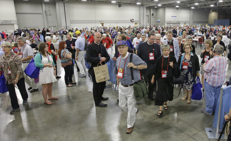 Deputies leave the hall after Episcopalians overwhelmingly voted to allow religious weddings for same-sex couples Wednesday, July 1, 2015, in Salt Lake City. The vote came in Salt Lake City at the Episcopal General Convention, just days after the U.S. Supreme Court legalized gay marriage nationwide. (AP Photo/Rick Bowmer)