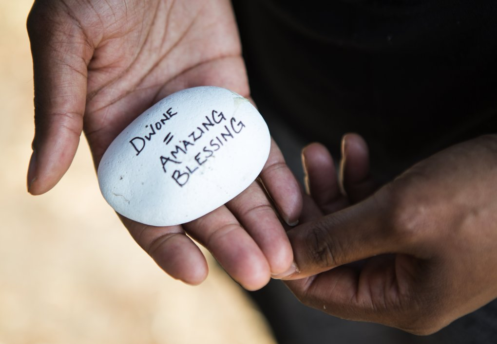 Falana Young-Wyatt holds a rock from a memorial near where her son was killed in Seattle's Leschi neighborhood. (Lindsey Wasson / The Seattle Times)