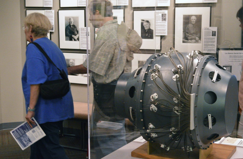 "This Monday, July 13, 2015 photo shows visitors to the Bradbury Science Museum in Los Alamos, N.M., walk by a replica of ""the gadget"". The gadget was the atomic bomb tested at the Trinity Test Site on July 16, 1945. Thursday marks the 70th anniversary of the Trinity Test in southern New Mexico and comes amid renewed interest in the Manhattan Project thanks to new books, video oral histories and a WGN America television drama series. (AP Photo/Russell Contreras)"